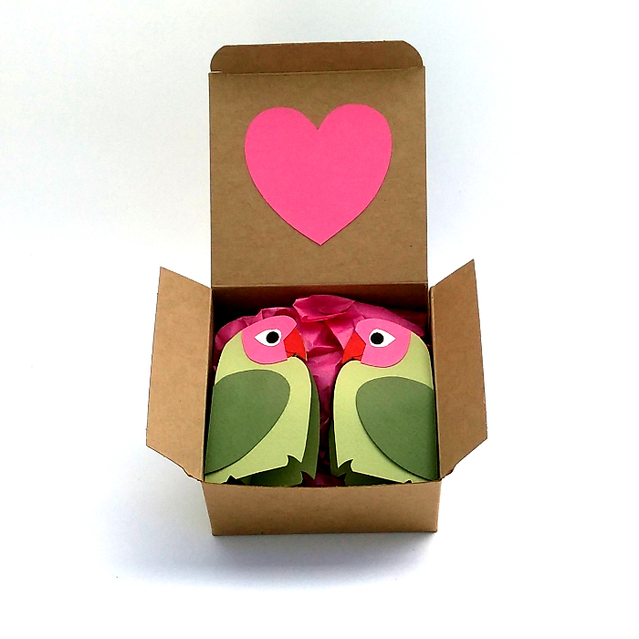 two green paper lovebirds in a gift box