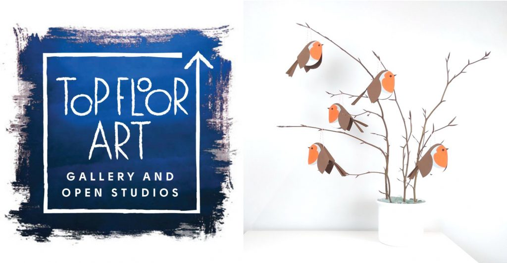 Logo for Top Floor At Gallery next to a photograph of paper robins hanging on an ornamental twig arrangement